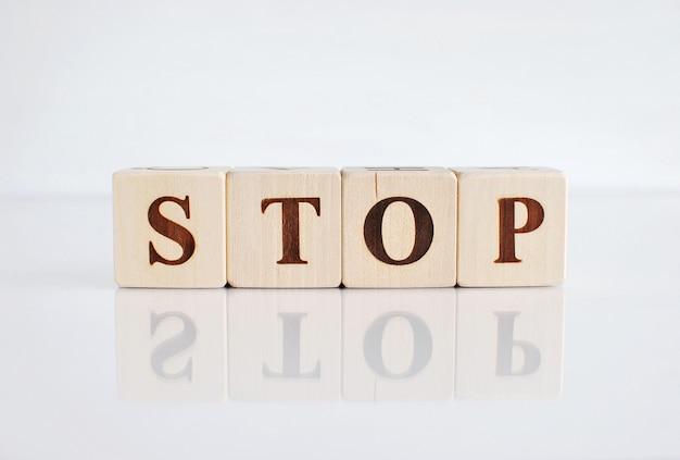 Exprima a parada em blocos de madeira, fundo branco com reflexão.