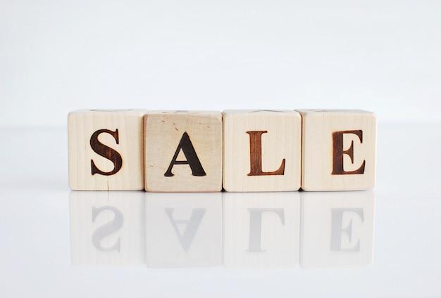 Exprima a venda feita com cubos de madeira, fundo branco com reflexão.