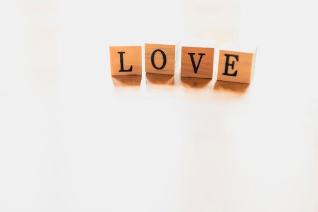 Exprima o amor em dados de madeira e no fundo branco.