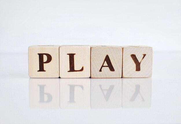 Exprima o jogo feito com cubos de madeira, fundo branco com reflexão.