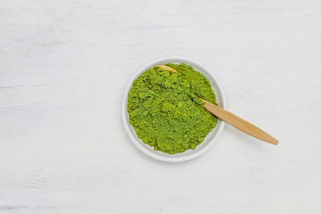 Exprima o matcha feito da colher em pó do chá verde e do bambu do matcha no branco. cópia de