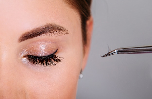 Extensão de cílios, mulher bonita, close-up e pinça