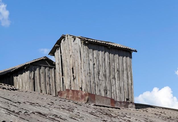 Extensões antigas no telhado de um prédio antigo feito de tábuas e troncos no campo, close-up contra um céu azul