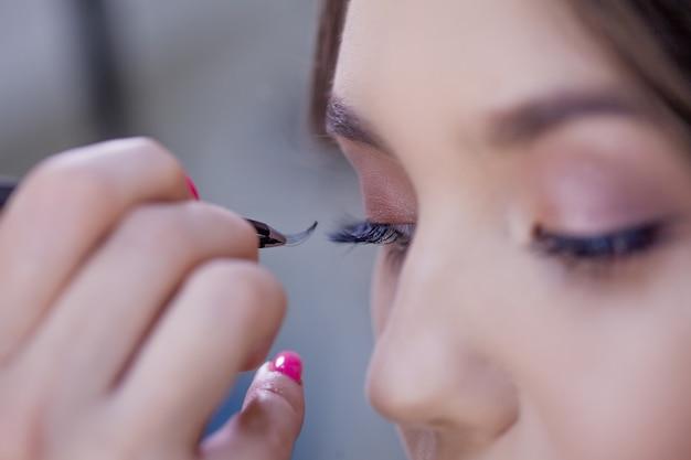 Extensões de cílios, maquiagem linda de um maquiador, uma imagem para uma sessão de fotos. close-up, maquiador com pinças fazendo extensões de cílios, um monte de cílios artificiais