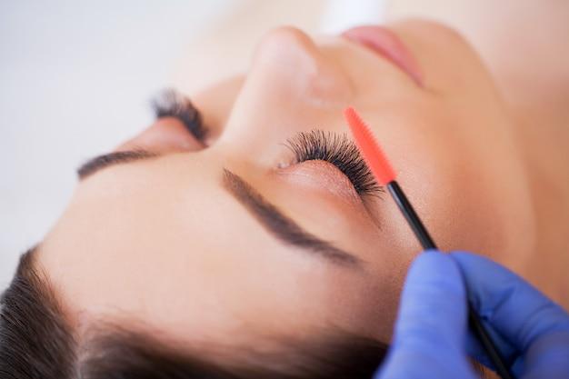 Extensões de cílios. pestanas falsas. procedimento de extensão de cílios. estilista profissional alongamento cílios femininos. mestra e cliente em salão de beleza