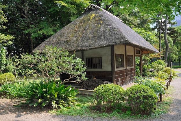 Exterior de cabana tradicional japonesa com telhado de palha em ambiente natural