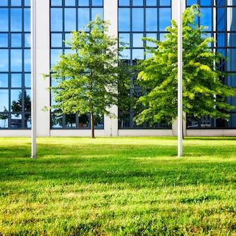 Exterior de prédio de escritórios de vidro moderno. quintal com relva e árvores. conceito de negócios e sucesso