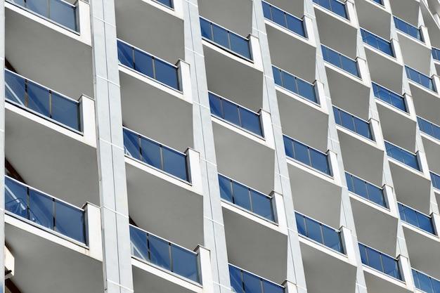 Exterior de um arranha-céu com janelas azuis e divisórias de concreto.