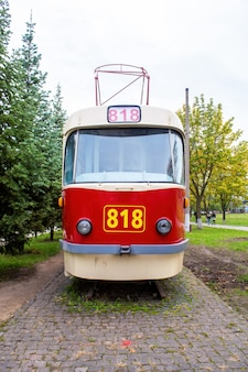 Exterior de um bonde vintage vermelho e branco na ferrovia como uma exposição com número 818, vegetação ao redor, chisinau, moldávia
