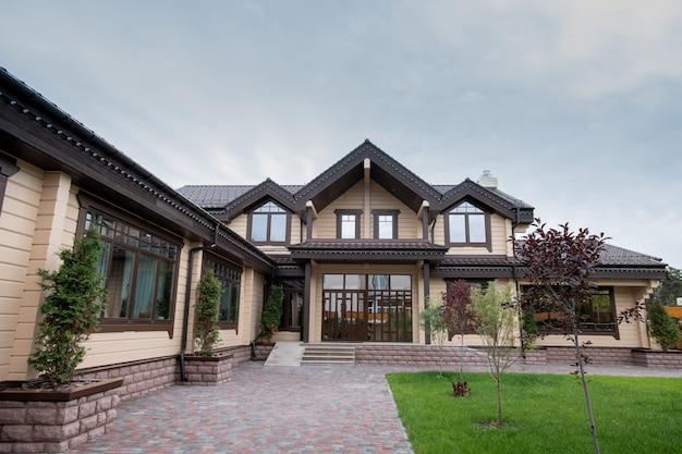 Exterior de uma casa ou casa de campo confortável e moderna com jardim na frente e pequenas árvores decorativas ao longo das paredes