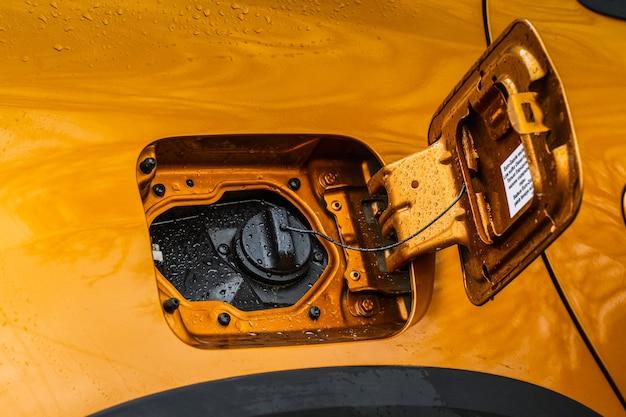 Exterior do carro com a porta do depósito de combustível aberta. a tampa do tanque de combustível de um carro foi aberta para abastecer gasolina ou diesel no tanque. a porta do tanque de combustível está aberta e a tampa do tanque de combustível fechada do carro