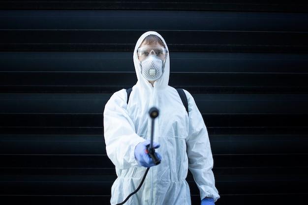 Exterminador profissional apontando bico pulverizador para controle de pragas para a câmera