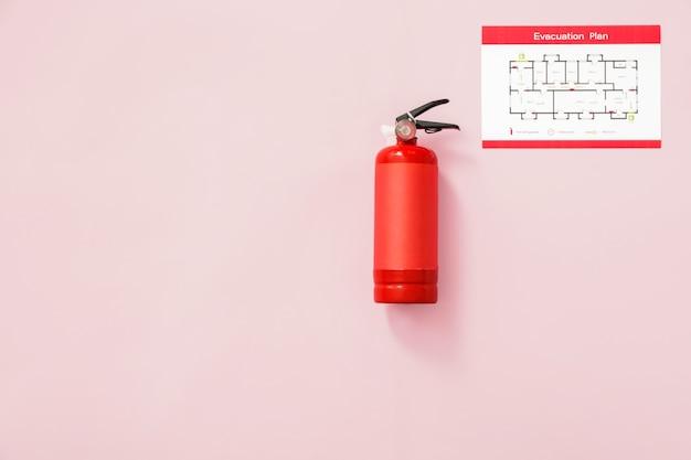 Extintor de incêndio e plano de evacuação na parede rosa