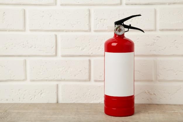 Extintor de incêndio em parede de tijolo branco