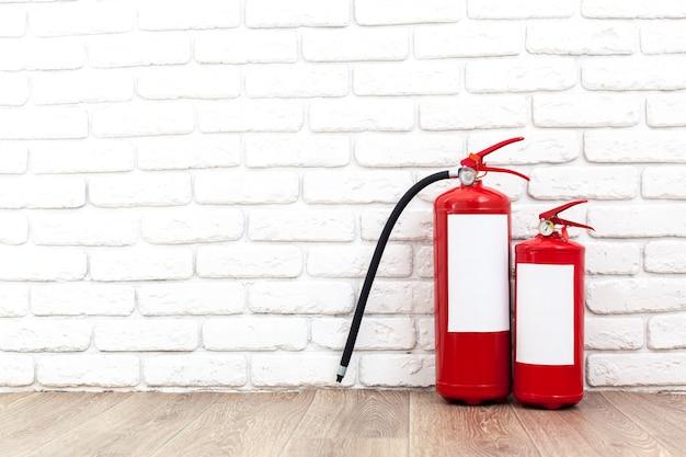 Extintor de incêndio perto da parede branca, pronto para uso