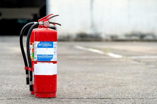 Extintor de incêndio vermelho do close up com macio-foco e sobre a luz no fundo