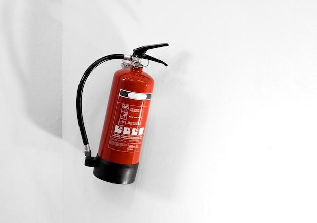Extintor de incêndio vermelho em parede branca