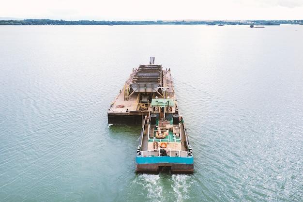 Extração de areia do rio, escavadeira extrai areia do fundo do lago e a descarrega em uma barcaça flutuante, mineração