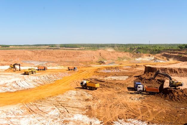 Extração de areia na pedreira. areia de carregamento de retroescavadeira em caminhões basculantes.