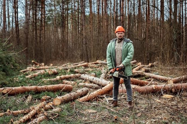 Extração de madeira, trabalhador em um traje de proteção com uma motosserra