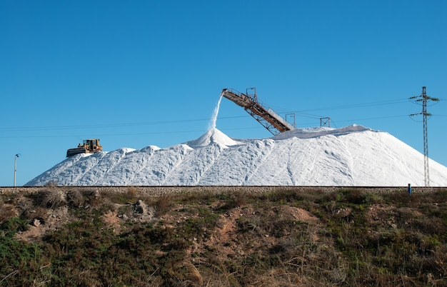 Extração de sal e despejando-o em uma grande pilha com a ajuda de um equipamento.