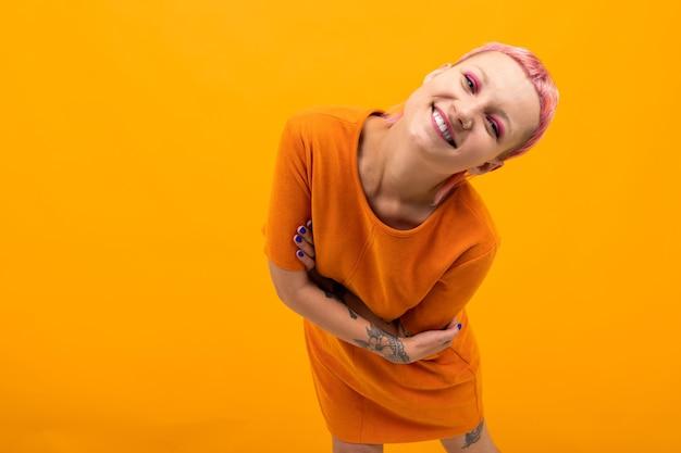 Extraordinária mulher bonita com cabelo curto rosa e uma grande tatuagem na mão com sorrisos isolados em fundo laranja