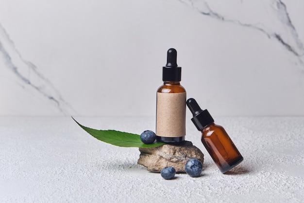 Extrato cosmético de mirtilo para cuidados com a pele para spa, vitaminas para a saúde, efeito fresco, tubo branco com creme ecológico natural para a pele do rosto. cosméticos orgânicos. ingredientes de mirtilo, garrafa marrom em suporte de pedra