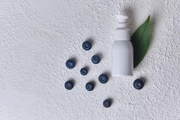 Extrato cosmético de mirtilo para cuidados com a pele para spa, vitaminas para a saúde, efeito fresco, tubo branco com creme ecológico natural para a pele do rosto. ingredientes de mirtilo, dispensador de garrafa em plano de fundo texturizado branco
