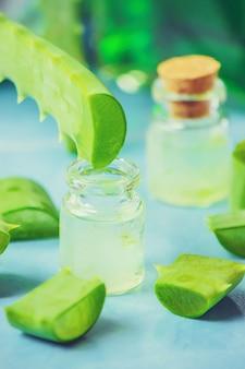 Extrato de aloe vera em uma pequena garrafa e peças em cima da mesa. foco seletivo.