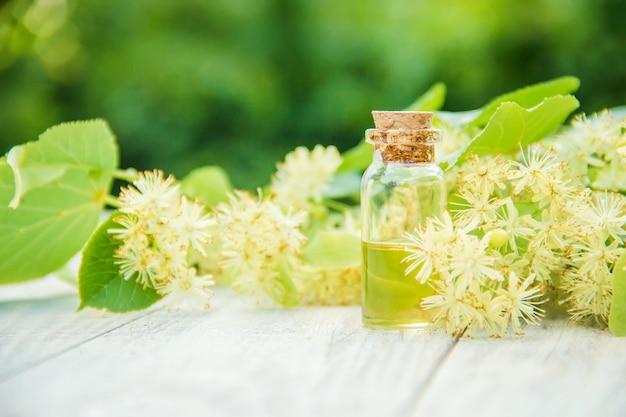 Extrato de tília e flores em uma pequena garrafa. foco seletivo.