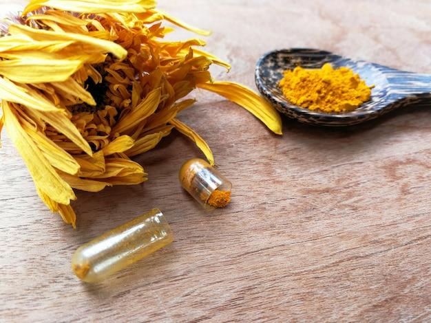 Extrato natural de açafrão para cápsulas de medicina erva na colher amarelo pétalas de calêndula em madeira