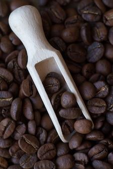 Extremamente close-up de grãos de café derramando fora da colher de madeira na mesa de madeira, ficus seletivo