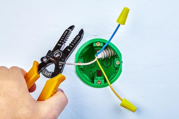 Extremidades de corte da fiação de cobre da caixa de saída para luz de parede por meio de um cortador decapador.