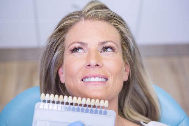 Extremo close-up médico segurando equipamento de clareamento dentário por paciente sorridente