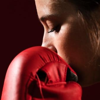 Extremo close-up retrato de uma mulher com luvas de caixa