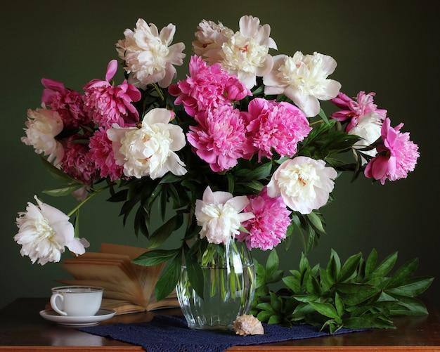 Exuberante buquê de peônias rosa e brancas em um vaso de vidro.