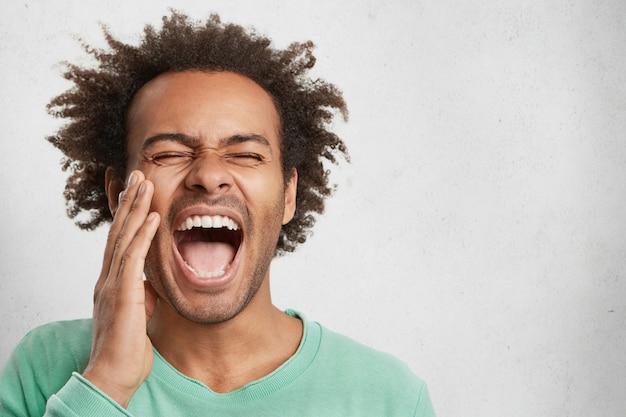Exultante, animado, feliz mestiço, homem abre bem a boca, fecha os olhos e grita de alegria