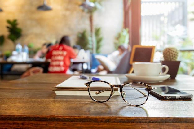 Eyeglasses e telefone celular selecionados do foco na tabela de madeira.