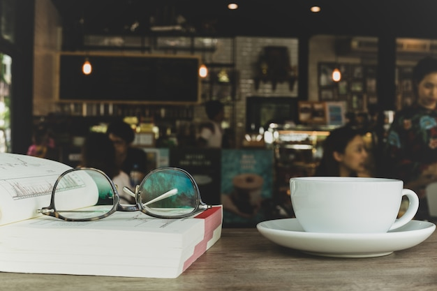 Eyes vidros no livro com a xícara de café na mesa de madeira no borrão.