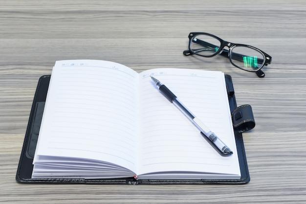 Eyewear, pena e diário aberto na mesa