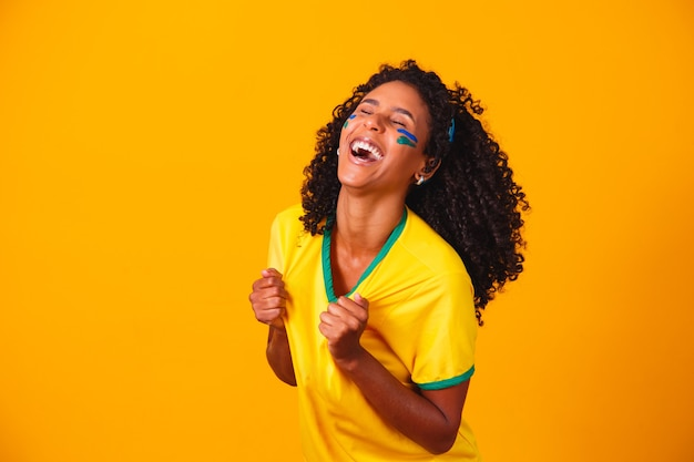 Fã brasileira. fã brasileiro comemorando futebol ou jogo de futebol em fundo amarelo. cores do brasil.