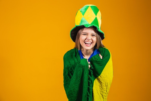 Fã brasileira loira comemorando em fundo amarelo com a bandeira do brasil