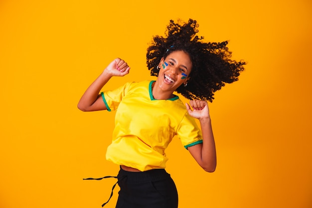 Fã brasileira. pulando para comemorar, torcedor brasileiro comemorando futebol ou jogo de futebol em fundo amarelo. cores do brasil.