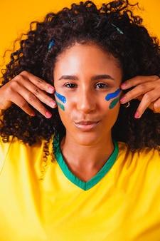 Fã brasileira. usando tinta como maquiagem, fã brasileiro comemorando futebol ou jogo de futebol em fundo amarelo. cores do brasil.