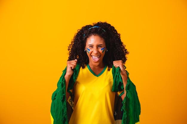 Fã brasileira. vestindo a bandeira brasileira em um retrato, fã brasileiro comemorando futebol ou jogo de futebol em fundo amarelo. cores do brasil. copa do mundo