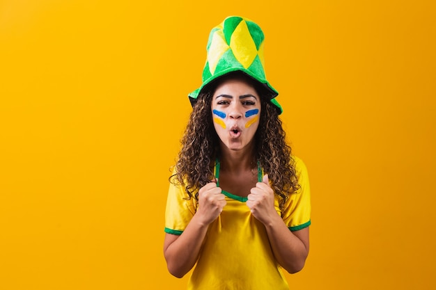 Fã brasileiro. fã brasileiro comemorando futebol ou jogo de futebol em fundo amarelo. cores do brasil.