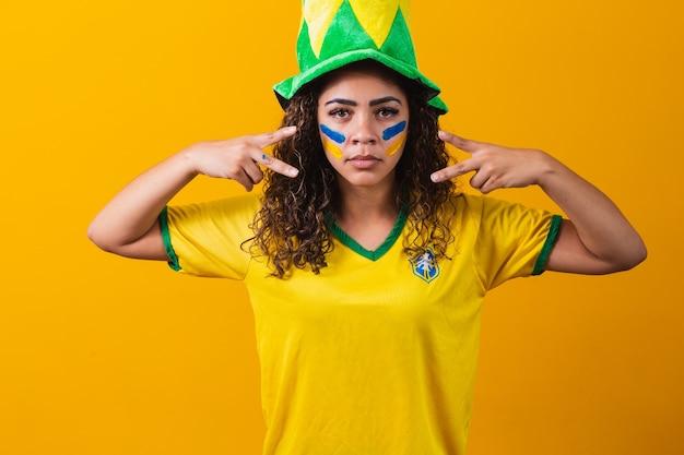 Fã brasileiro. usando tinta como maquiagem, fã brasileiro comemorando futebol ou jogo de futebol em fundo amarelo. cores do brasil.