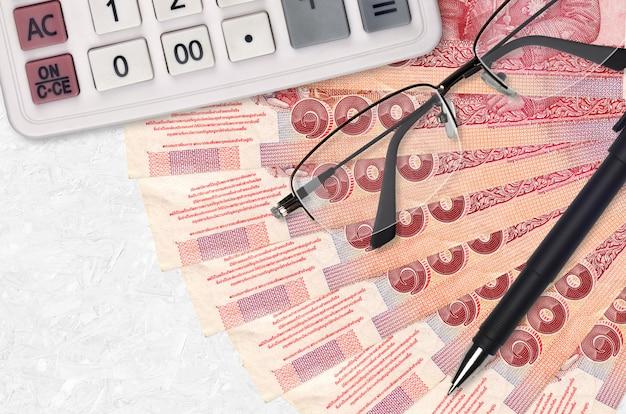 Fã de 100 contas de baht tailandês e calculadora com óculos e caneta. empréstimo empresarial ou conceito de época de pagamento de impostos