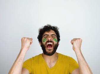 Fã de esporte com a maquiagem de bandeira do Brasil no rosto comemorando o triunfo de sua equipe