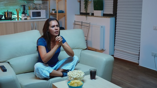 Fã de esportes animado, assistindo a jogos online na tv, sentado no sofá. senhora sozinha em casa de pijama apoiando o time favorito de fotball e gritando na competição. curtindo a noite na frente da televisão.